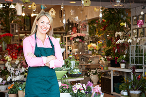 Woman working in florist standing outside store smiling